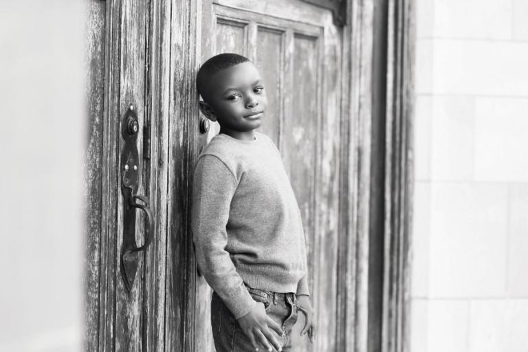 boy near wooden door by Carrollton children's photographer