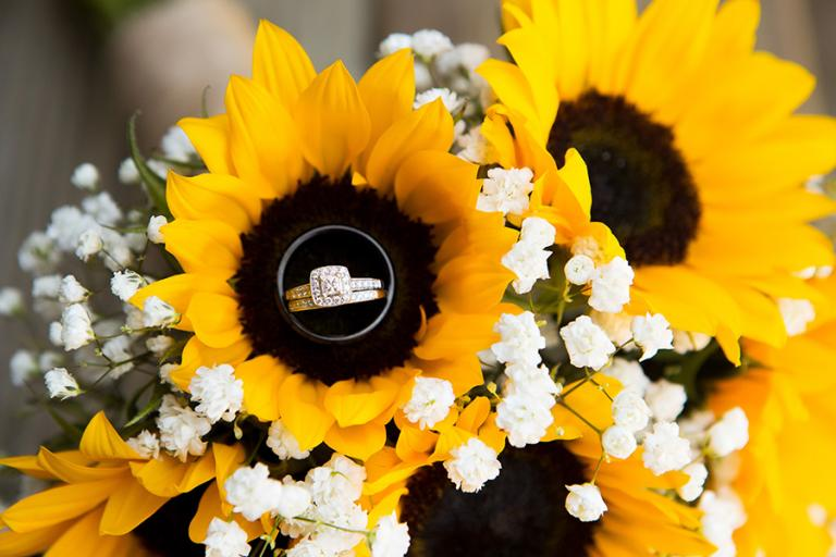 wedding rings in a sunflower buoquet by Atlanta wedding photographer