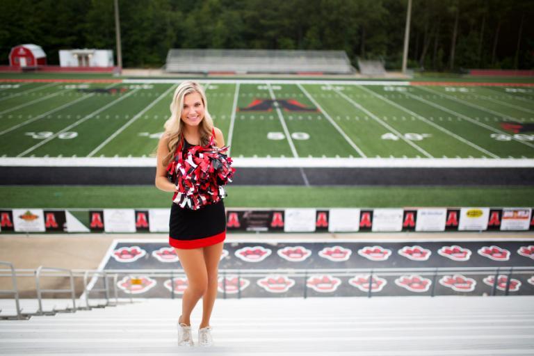 Douglasville senior portrait photographer, cheerleader at Alexander High football field