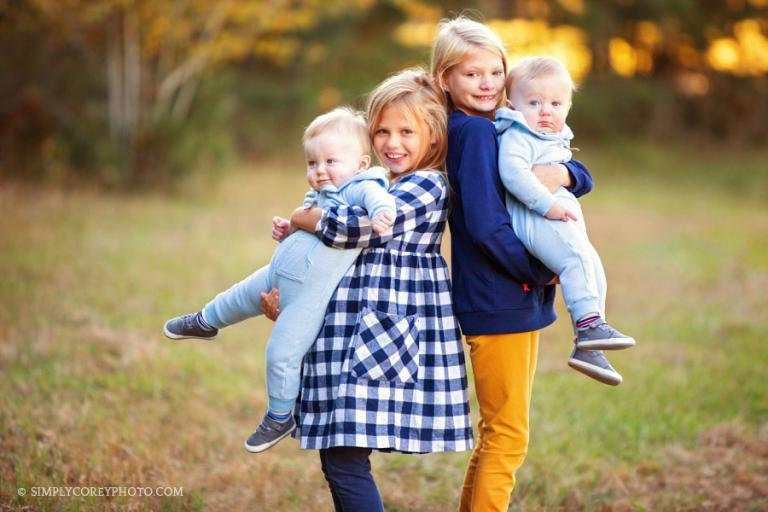 Newnan family photographer, sisters holding twin baby brothers