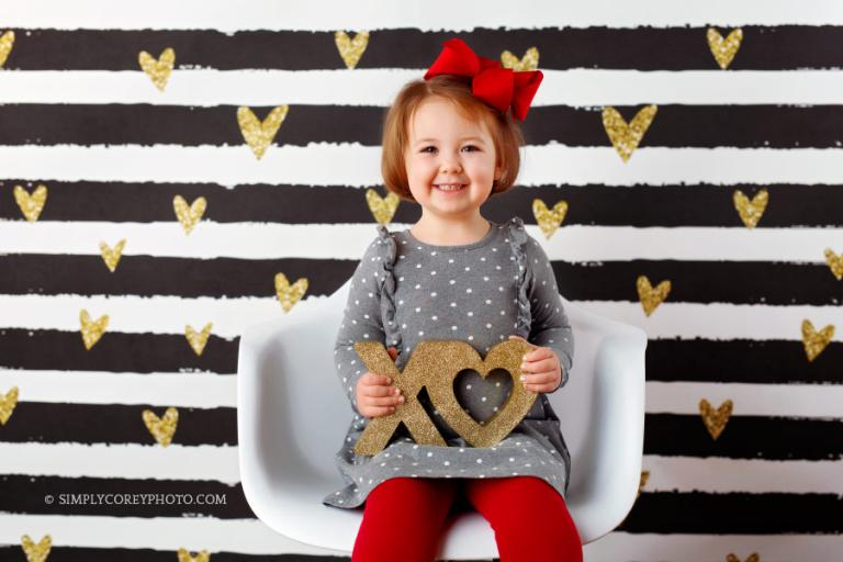 West Georgia Valentine's Day Mini Sessions photographer, girl on black and gold backdrop