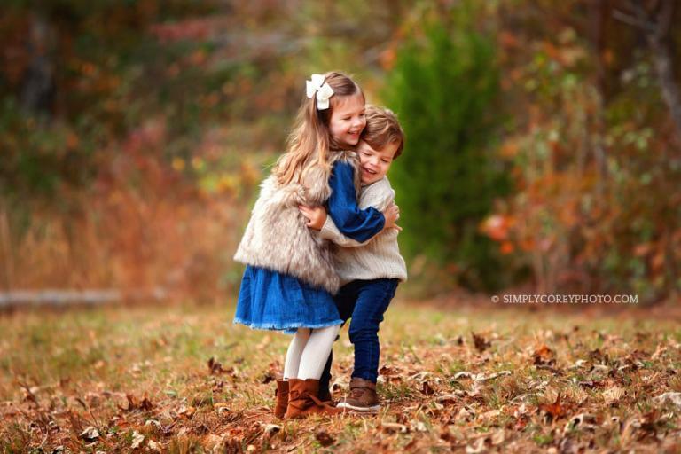 Atlanta family photographer, children hugging outside in the fall