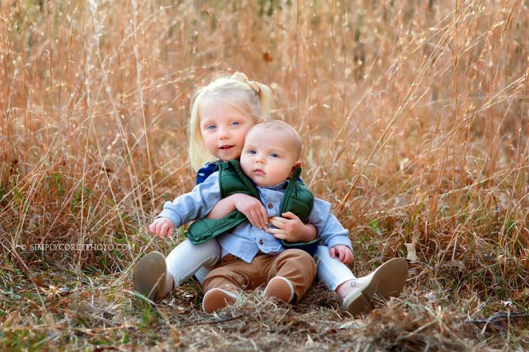 Newnan family photographer, sister holding baby brother in tall golden grass