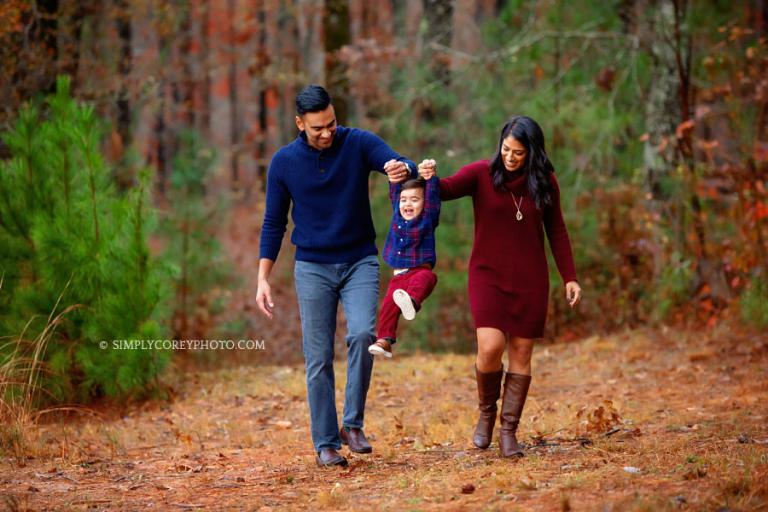 Villa Rica family photographer, parents swinging baby outside