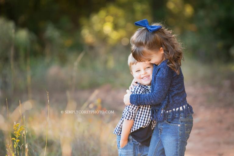 Outdoor photo of siblings hugging by Atlanta family photographer