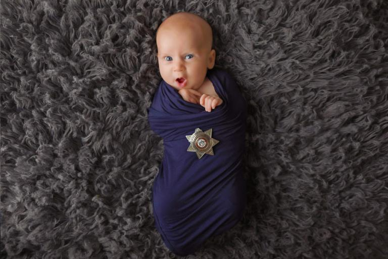 Newnan newborn photographer, baby with police badge making a funny face