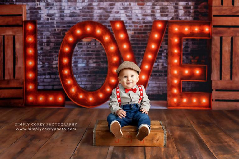 Atlanta baby photographer, marquee love sign with baby in suspenders