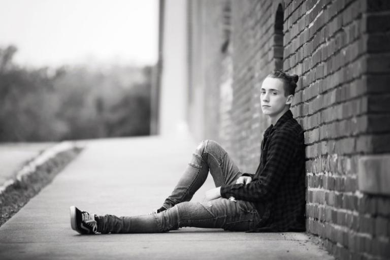 Douglasville senior portrait photography, teen boy by a brick wall downtown
