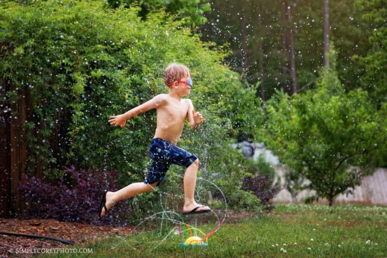 Atlanta lifestyle photographer, boy in summer running through a sprinkler with goggles on