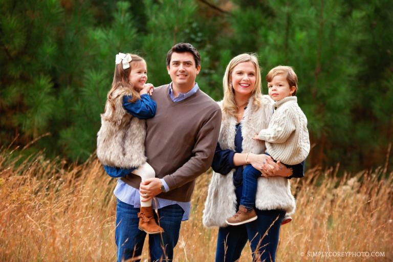 Newnan family photographer, parents holding kids in front of pine trees
