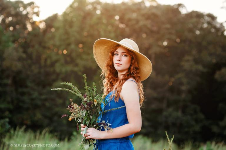 Douglasville senior photographer, teen outside in a floppy hat with flowers