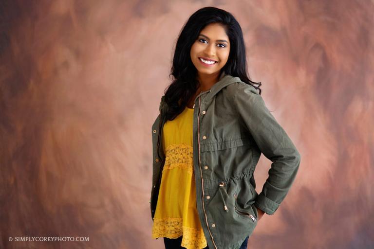 Douglasville senior portrait photographer, teen wearing a green jacket in studio