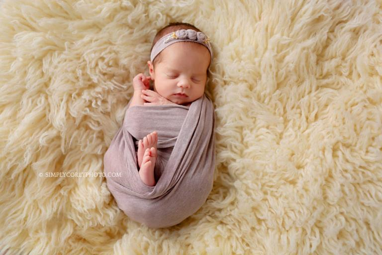 newborn photographer Carrollton, Georgia; baby in a purple wrap on a flokati
