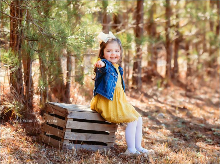 Carrollton child photographer, girl outside near pine trees
