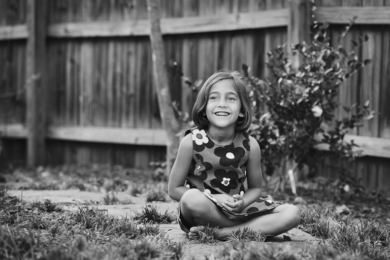 Carrollton children's photographer, child sitting on sidewalk at home