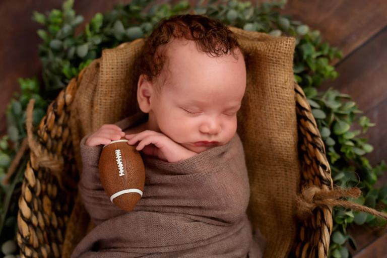 Douglasville newborn photographer, baby boy holding a football