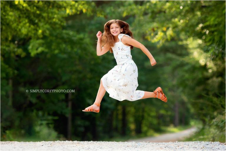 Atlanta children's photographer, tween jumping on country road