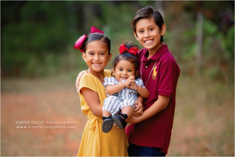 Newnan family photographer, kids holding baby sister outside