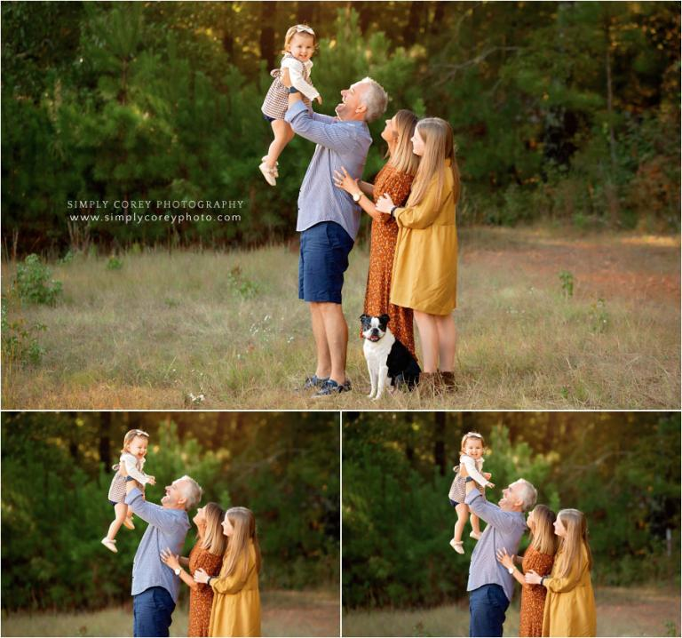 Atlanta family photographer, dad lifting toddler up in a field
