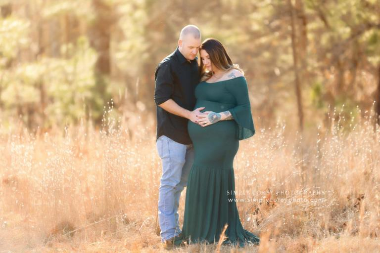 Douglasville maternity photographer, couple outside looking at belly
