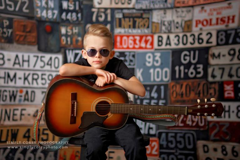 Atlanta photographer, child in sunglasses with guitar on license plate backdrop